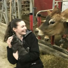 Victoria Ryan holding a cat and smiling at a cow